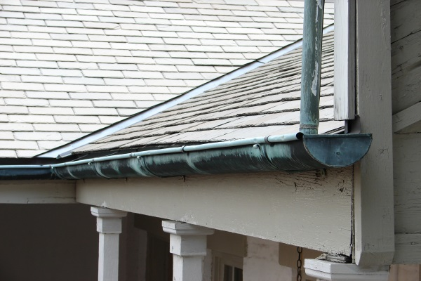 an old gutter system attached to a shingle roof