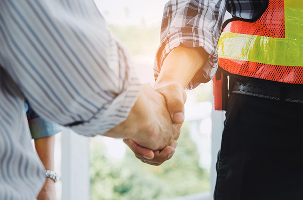 homeowner and roofing contractor shaking hands