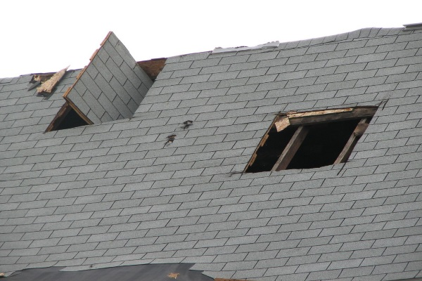 an immensely damaged asphalt shingle roof