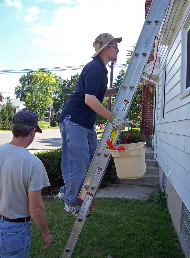 young man climbing ladder to clean gutters