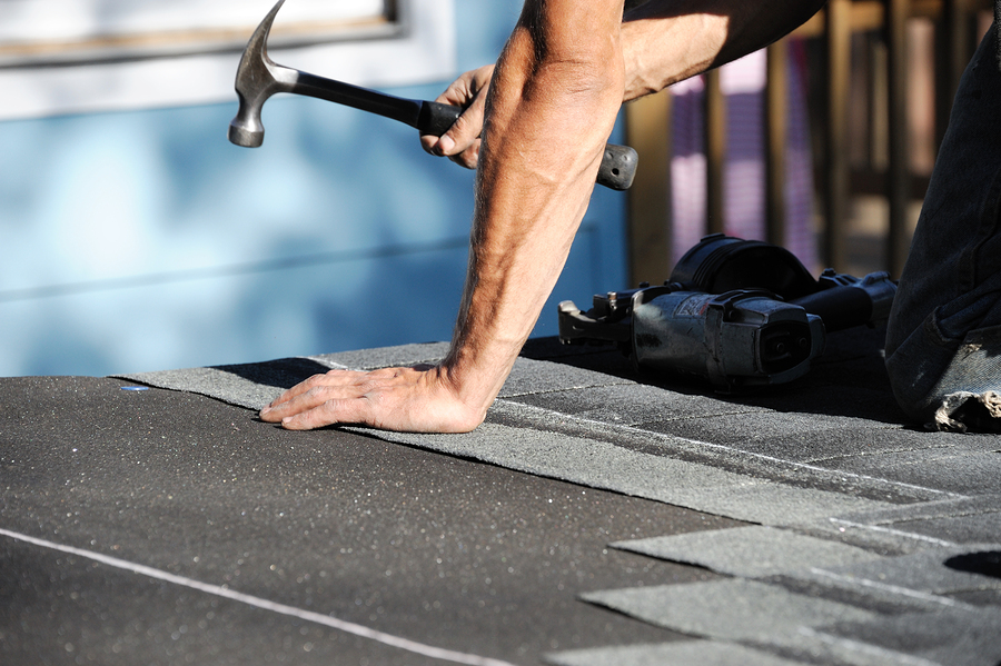 a roofer working on repairing a damaged roof
