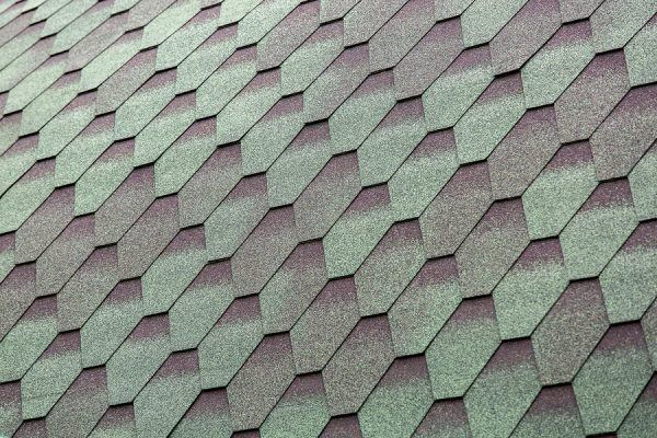 Close up view on asphalt roofing gray green color shingles gradient pattern